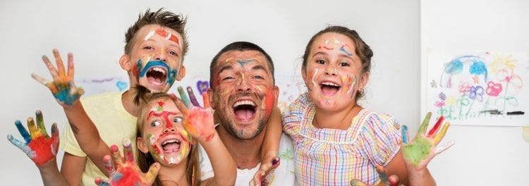 children and adult with paint on hands and face