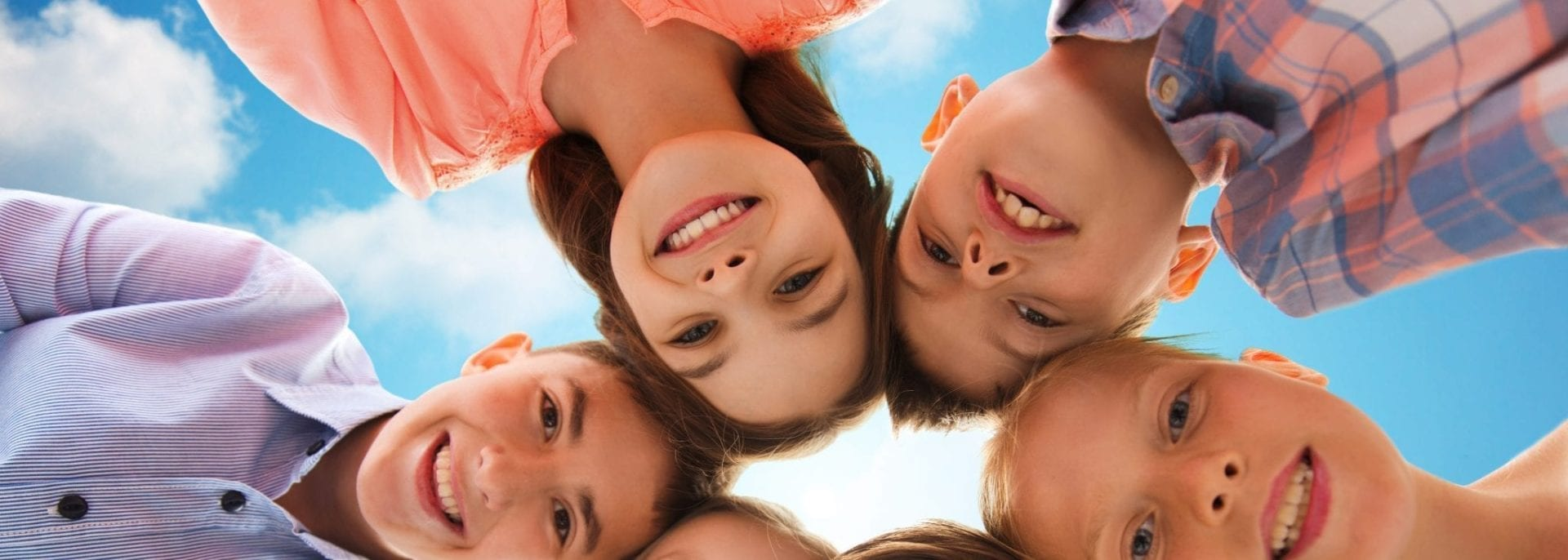 6 children looking down at camera smiling - News