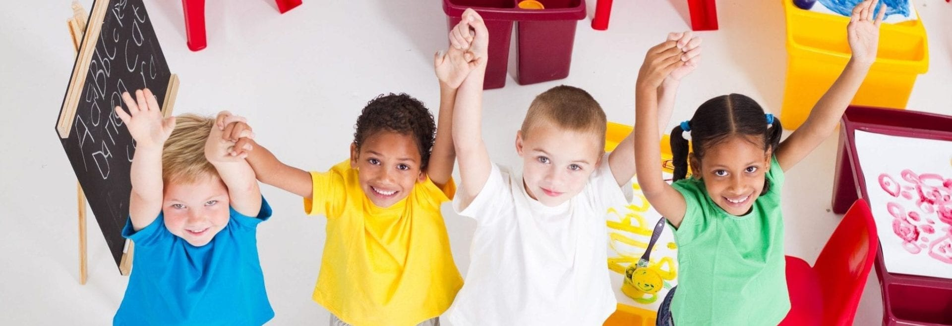 4 young children smiling with hands up