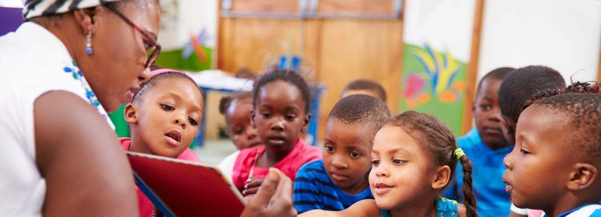 teacher reading book to preschool students