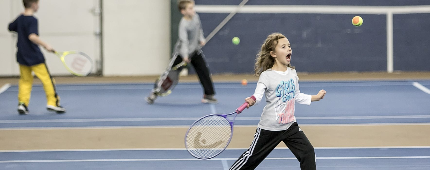 young girl hitting tennis ball
