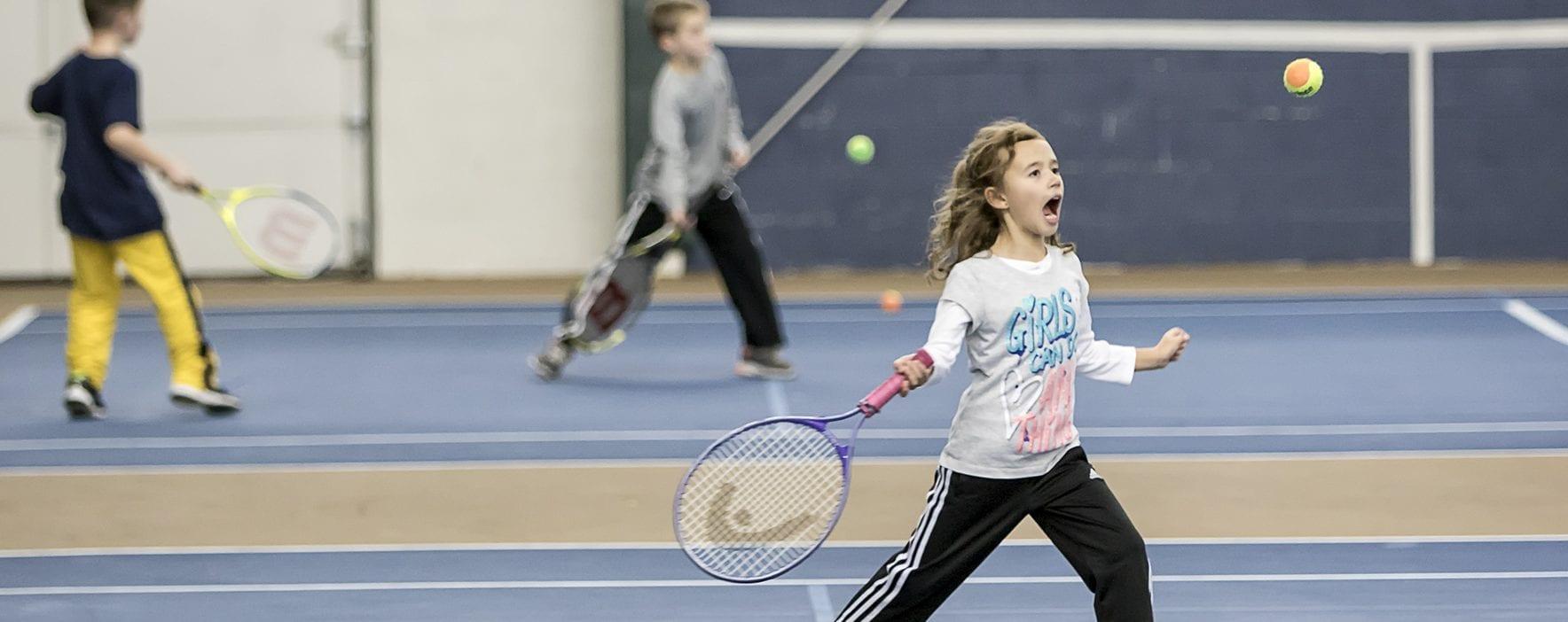 young girl hitting tennis ball