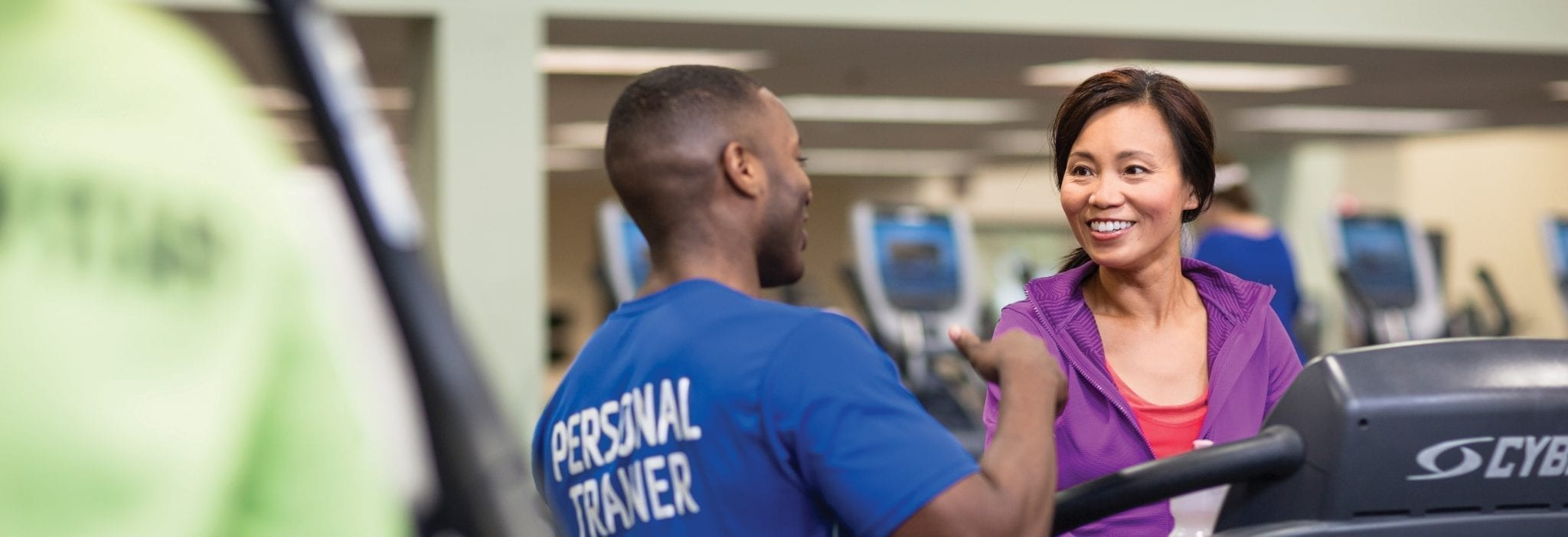 personal trainer working with lady on treadmill